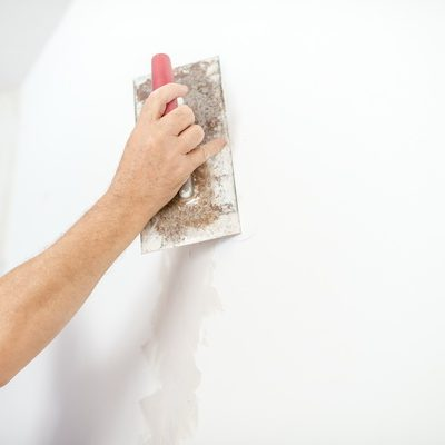 Man plastering a white wall preparing it for painting or wallpapering in a DIY and home decoration or renovation concept.